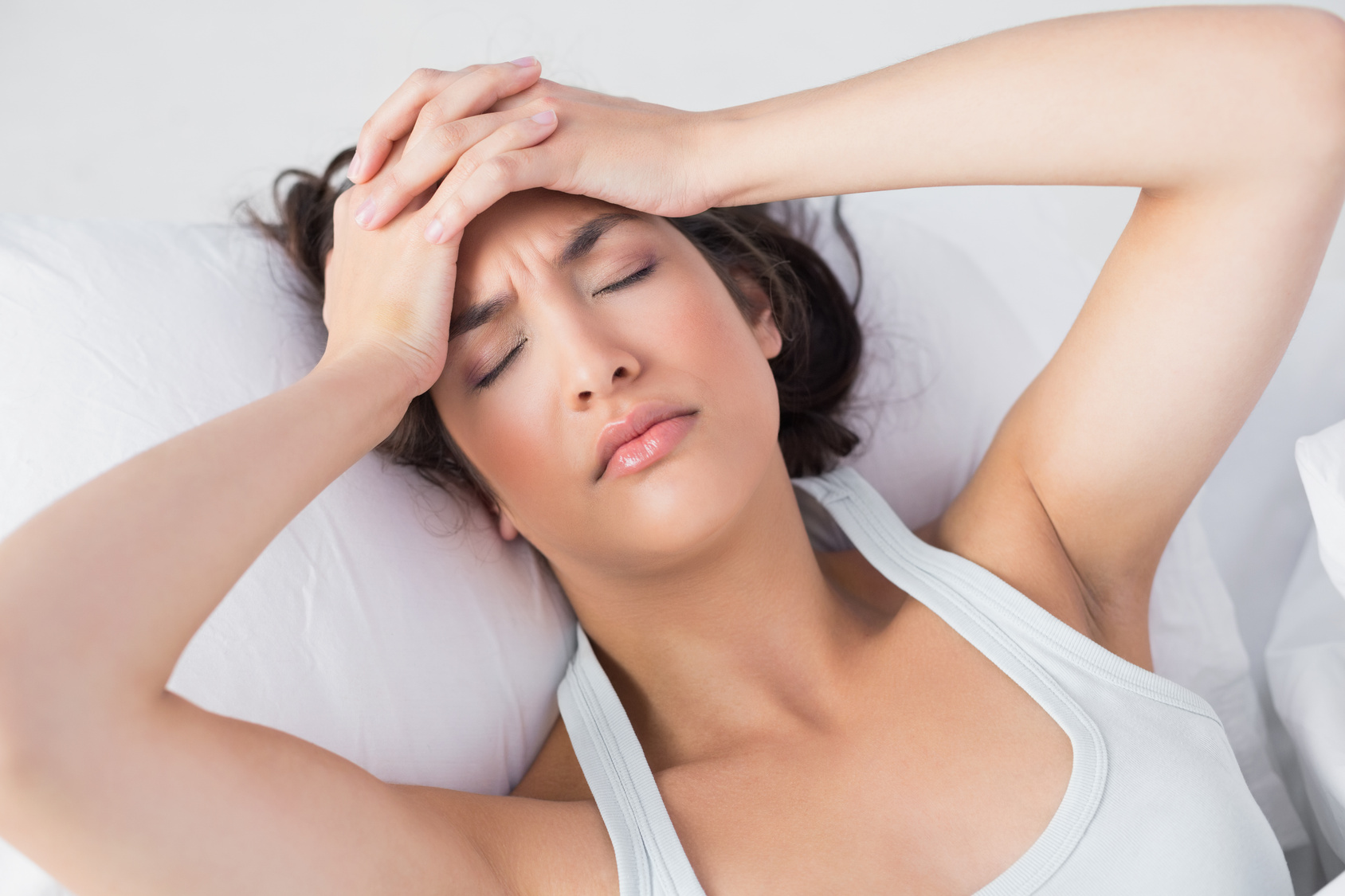 High angle view of a sleepy young woman suffering from headache with eyes closed in bed at home
